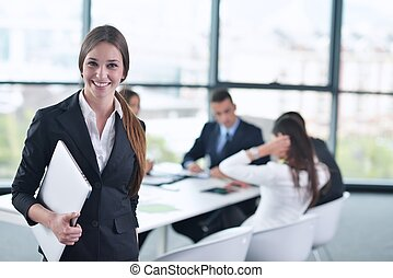 business woman with her staff in background at office -...