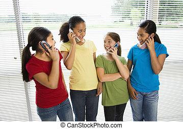 Girls on phones. - Preteen girls of mutiple ethnicities...