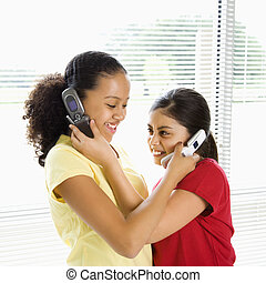 Girls on cell phones. - Two preteen girls holding cell...