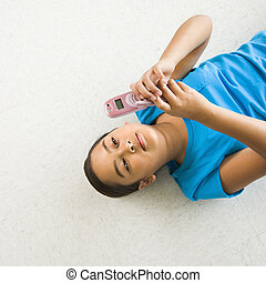 Girl text messaging. - Asian preteen girl lying on back on...