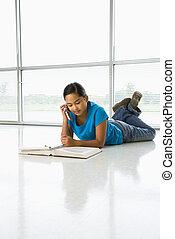 Girl doing homework. - Asian preteen girl lying on floor...