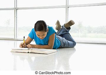 Preteen girl. - Asian preteen girl lying on floor doing...
