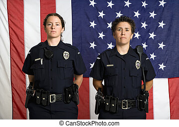 Policewomen and flag. - Portrait of two mid adult Caucasian...