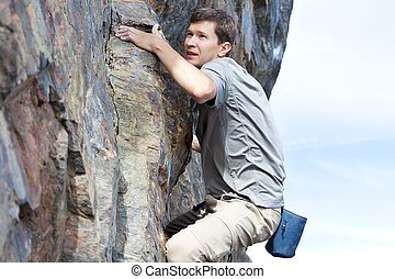 bouldering outdoors - young man bouldering or rock climbing...