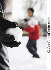 Snowball fight - Boy holding snowball ready to throw at boy...