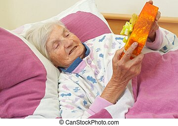 The gift - Happy elderly woman holding a present in the bed