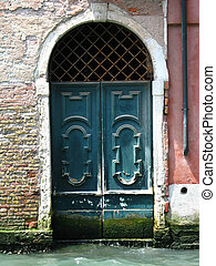 Sinking Venice - Old doors in Venice sinking to canal water