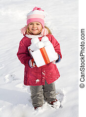 Happy little girl with a box of snowballs in winter time