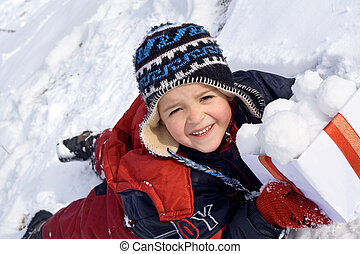Happy kid with snowballs in a box