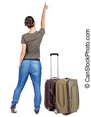 Back view of traveling pointing woman with suitcase. Rear...