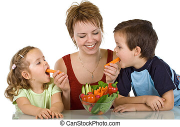 Happy kids eating vegetables - Woman feeding kids with...