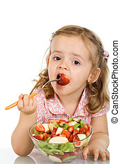 Little girl eating fruit salad - healthy food concept -...