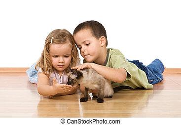 Kids with their kitten on the floor