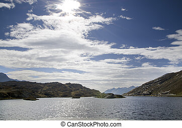Panoramic view over mountain and a lake with blue sky and...