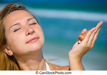 Woman on the tropical beach - Young woman with seashells on...