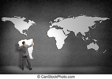 businessman attaches to the wall of the continents