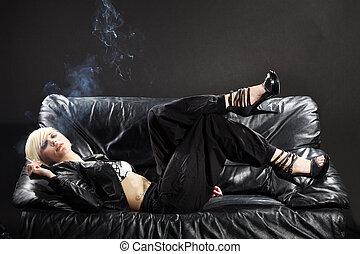 pretty woman smokes cigarette on couch