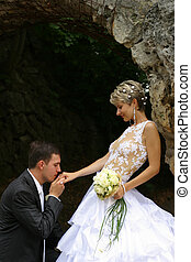 Newly married pair - The groom kisses a hand to the bride...