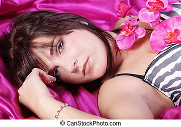 pretty woman with orchid in bed