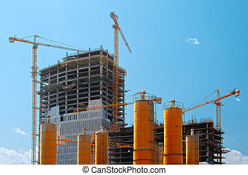 tall buildings under construction with cranes against a blue...