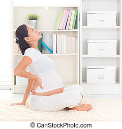 Back pain Eight months pregnant Asian woman holding her back...