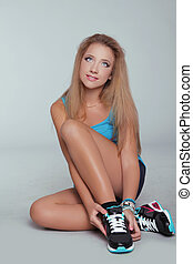 Young teen girl sitting with Sporty sneakers shoes. Studio...