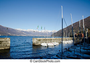Small port with boats and snow-capped mountains - Small...
