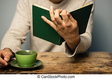 Man is reading and having coffee