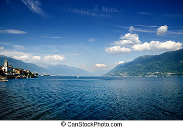 Lake with mountains and blue sky with clouds in brissago...