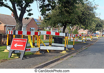Road work warning signs and barriers in a street in England...