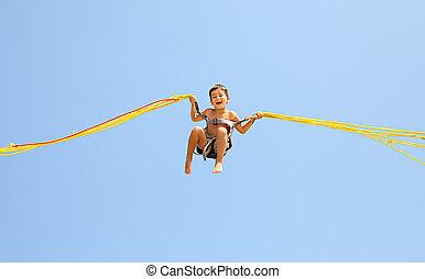 Boy jumping on trampoline - Little boy jumping on a...