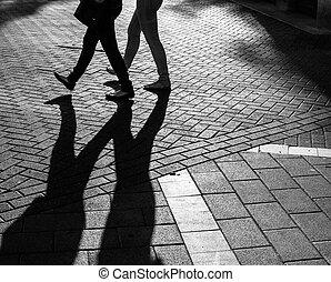Shadows of people walking street in morning light