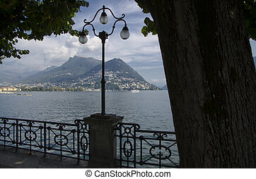 Lake front with trees and a street lamp on an alpine lake...