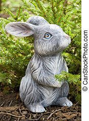 rabbit statue on green pine tree backgound