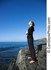 Woman meditating - Caucasian mid-adult woman standing on...