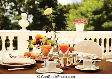 rich breakfast on the balcony - table set for an outdoor...