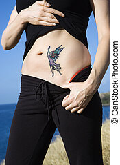 Woman with fairy tattoo - Caucasian woman exposing tattoo of...