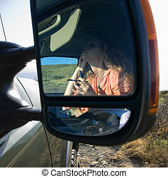 Woman doing make up in car. - Reflection in vehicle side...