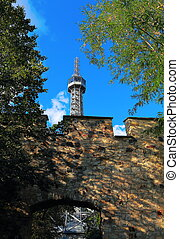 Petrin tower in Prague near stone wall and among the trees...