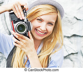 Portrait of smiling hipster girl making photo with retro...