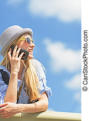 Smiling hipster girl talking mobile phone and looking on...