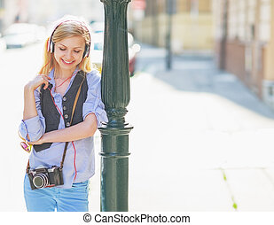 Happy hipster girl listening music on city street
