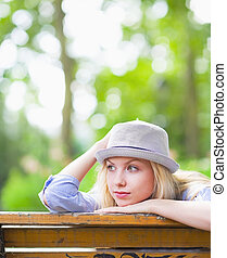 Thoughtful hipster girl sitting on bench in the park and looking on copy space
