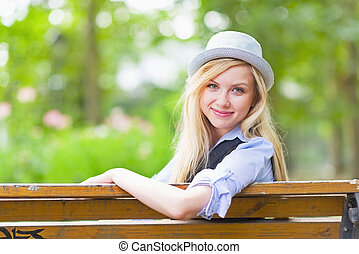 Smiling hipster girl sitting on bench in the city park