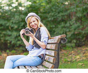 Smiling hipster girl with retro photo camera sitting on bench in the park