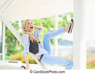 Smiling hipster girl having fun while sitting on urban structure