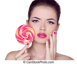 Bright makeup. Beauty Girl Portrait holding Colorful lollipop. Pink Lips. Nail polish manicured nails. Skin care