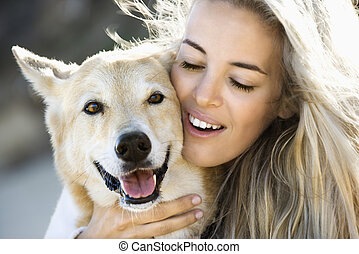 Woman petting dog - Pretty Caucasian blond woman hugging...