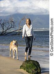 Woman walking dog - Caucasian woman walking brown dog on...