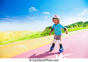 Happy boy rushing downhill on rollerblades - Happy thee...